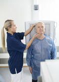 Radiologist Adjusting Head Of Male Patient Before Taking Xray Stock Photos