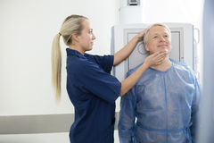 Radiologist Adjusting Head Of Mature Patient Before Taking Xray Royalty Free Stock Images