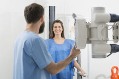 Radiologist Adjusting X-ray Machine On Female Patient At Hospita Stock Images