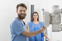 Radiologist Adjusting X-ray Machine Over Female Patient In Hospi Royalty Free Stock Photography