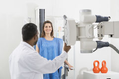 Radiologist Adjusting X-ray Machine Over Female Patient Stock Images
