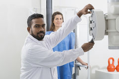 Radiologist Adjusting X-ray Machine Over Patient In Hospital Stock Photos