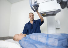 Radiologist Adjusting Xray Machine Over Man Royalty Free Stock Photography