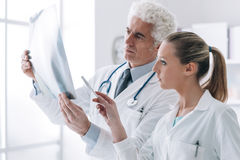 Radiologist checking an x-ray with his assistant Royalty Free Stock Photography