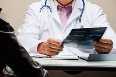 Radiologist At Desk Holding X-ray Stock Photography