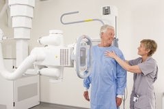 Radiologist helping patient with x-ray machine Stock Photos