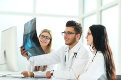 Radiologist and his colleagues discuss the x-ray of the patient stock photography