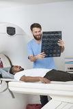 Radiologist Holding X-ray Report While Patient Lying On CT Scann Royalty Free Stock Photo
