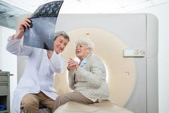 Radiologist With Patient Looking At CT Scan. Mature male radiologist with an elderly female patient looking at CT scan results Stock Photo