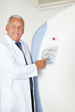 Radiologist pressing button on MRI. Smiling radiologist doctor pressing button on MRI machine royalty free stock photo