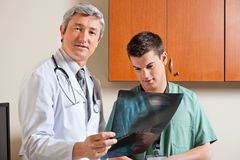 Radiologist Standing With Male Technician. Portrait of mature radiologist holding shoulder x-ray while standing with male technician Royalty Free Stock Photography