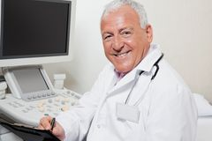 Radiologist Writing On Clipboard. Portrait of happy senior male radiologist writing on clipboard with ultrasound machine in background Royalty Free Stock Photos