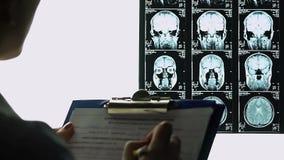 Radiologista fêmea que completa o relatório médico, descrevendo o mri dos cérebros, conclusão video estoque