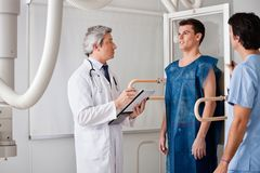 Radiologists Conducting X-ray On Male Patient Stock Images