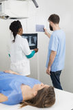 Radiologists Holding X-ray And Digital Tablet With Patient In Fo Royalty Free Stock Image