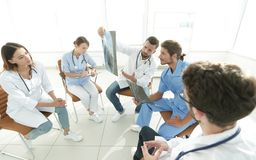 Radiologists and a surgeon discussing a radiograph of a patient Stock Photos