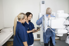 Radiologists Using Digital Tablet While Patient Standing At Xray Stock Photo