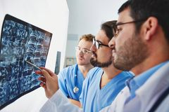 Radiologists at work. Young male doctors looking at x-ray and analyzing it Royalty Free Stock Photo