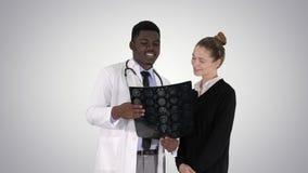 Radiologue de visite de jeune femme pour l'examen de rayon X de son cerveau sur le fond de gradient banque de vidéos
