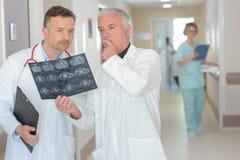Radiologues regardant le rayon X dans le couloir d'hôpital photographie stock libre de droits