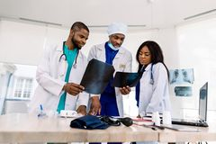 Free Radiology, People And Medicine Concept - Group Of Three African Doctors, Surgeon And Radiologists, Looking At And Stock Images - 160942974