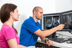 Radioloog die een patiënt councelling die beelden van tomograpy of MRI gebruiken Stock Foto