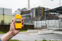 Radiometer in hand with fourth reactor on the background. Radiometer in hand with fourth Chernobyl reactor on the background Royalty Free Stock Image