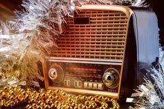 Radiomottagare i retro stil med julgarneringar och ljusa strålar på svart bakgrund Arkivbild