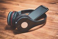 Radion lyssnar musikbegreppet med en svarta Smartphone som lutar på mot den svarta över huvudet headphonen på en trätabell Royaltyfria Bilder