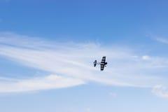 Radiosända det kontrollerade leksakflygplanet mot blå himmel med vita moln arkivbild