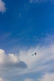 Radiosända det kontrollerade leksakflygplanet mot blå himmel med vita moln royaltyfri foto