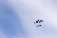 Radiosända det kontrollerade leksakflygplanet mot blå himmel med vita moln royaltyfri bild