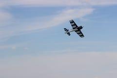 Radiosända det kontrollerade leksakflygplanet mot blå himmel med vita moln arkivfoton
