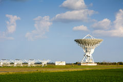 Radiotelescope: parabolic antenna and linear array antenna Stock Images