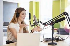 Radioutsändning för ung kvinna i en studio som gör en gest, nära övre arkivfoto