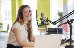 Radioutsändning för ung kvinna i en studio som ler till kameran royaltyfria bilder