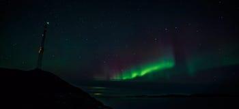 Radiowy wierza na północnych światłach nad fjord i wzgórzu Zdjęcie Stock