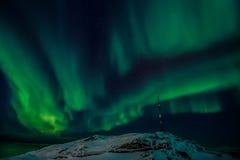 Radiowy wierza na wzgórzu i Północnych światłach nad fjord Obraz Stock