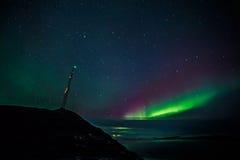 Radiowy wierza na wzgórzu zakrywających chmurami północnych światłach i Obraz Stock