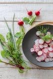Radis coupés en tranches d'un plat foncé sur une table en bois blanche photographie stock