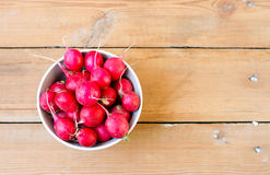 Radish in a bowl. On the wooden table Stock Photos