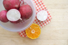Radish in bowl on wooden table. With sliced orange Royalty Free Stock Photo