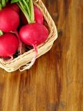 Radish with green tops in a wicker basket Royalty Free Stock Photos