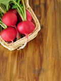 Radish with green tops in a wicker basket Stock Photo