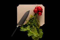 Radish with knife. On wooden cutting board on black background Royalty Free Stock Photography