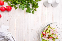 Radish salad. Radish salad in a glass bowl on a white wooden table. Frame Stock Photo