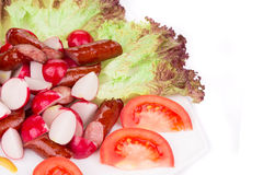 Radish salad with tomatoes and grilled sausages. Stock Photo