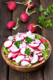 Radish salad on wooden table. Radish salad in bowl on wooden table Royalty Free Stock Photo