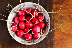 Radish on a wooden background. A bowl of fresh radishes on a wooden background Stock Photography