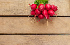 Radish on the wooden background. Ripe red radish  lying on a wooden background Stock Photos